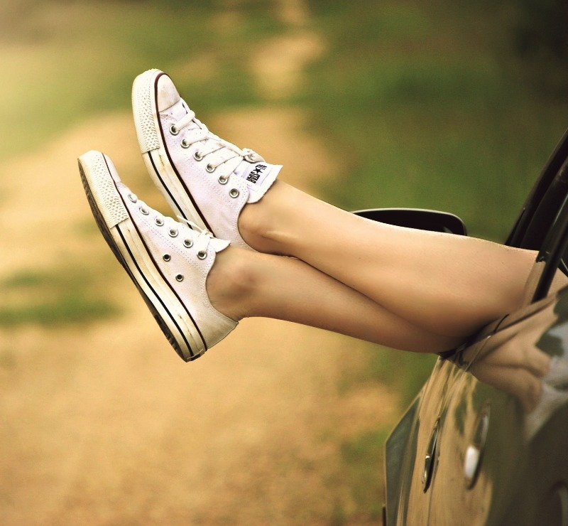relaxed businesswoman with legs out of car window